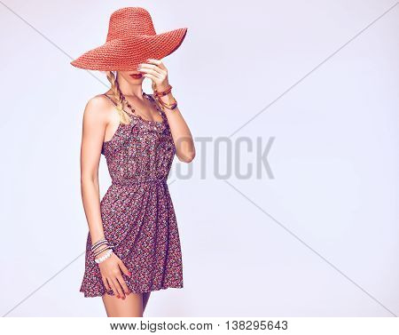 Hippie Boho woman Having Fun. Playful positive Model, Summer Fashion Outfit. Blonde in Trendy Sundress, pigtails, ethnic Fashion Accessories. Hat covers girl face, romantic Style.Unusual creative look