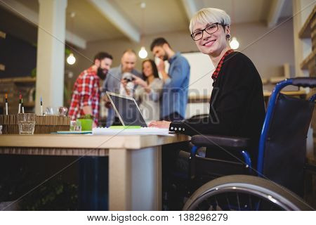 Portrait of happy disabled businesswoman using laptop at desk in creative office