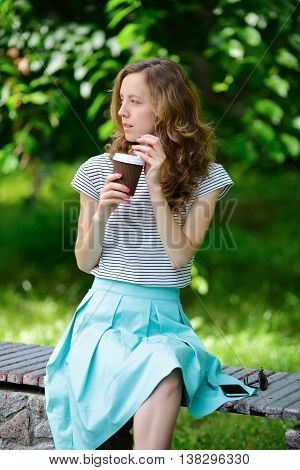 Woman with disposable coffee cup is sitting on a bench in the park. Summer outdoors