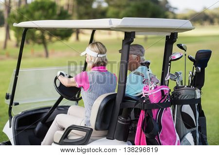 Mature woman driving golf buggy while sitting by man