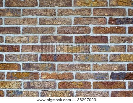 Background of Multi Colored Bricks with Cracked Surface and Concrete closeup Outdoors