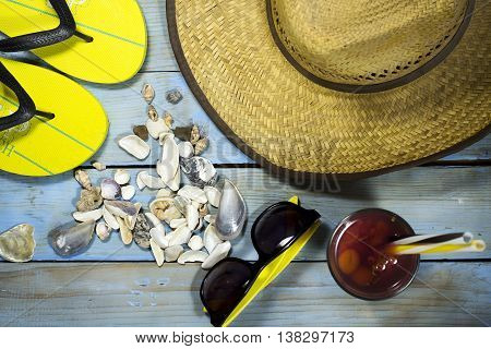 Fashion accessories summer flip flops hat sunglasses and seashells on a blue wooden background. Top view