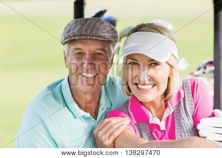 Portrait of cheerful golfer couple sitting in golf buggy