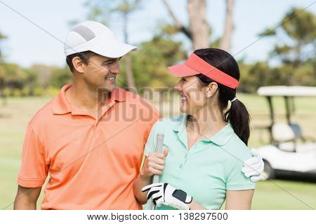 Happy golfer couple with arm around while standing on field