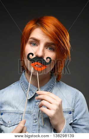 Portrait of young pretty girl with red hair wearing fake mustache and lips over grey background.