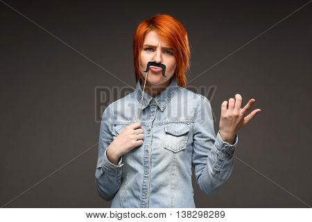 Portrait of young pretty girl with red hair wearing fake mustache over grey background. Copy space.