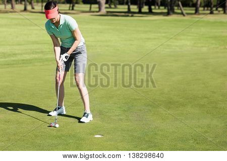 Full length of woman playing golf while bending on field