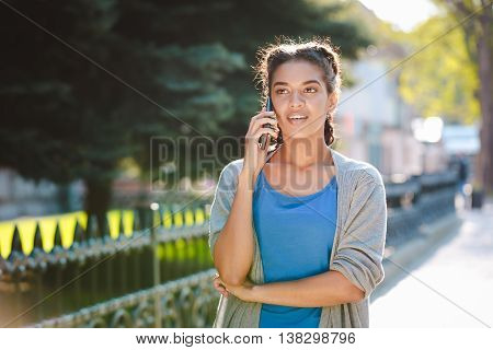 Charming dark skinned girl dressed in blue t-shirt and grey jacket  at the nature background and talking on her phone with smile.