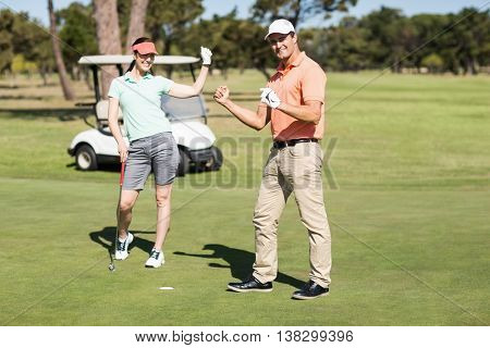 Full length portrait of golfer couple celebrating success while standing on field