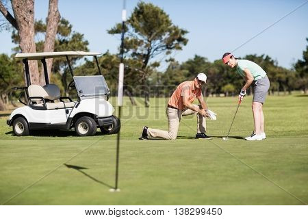 Full length of couple playing golf on sunny day