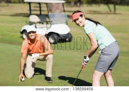 Portrait of smiling woman playing golf while standing by man on field