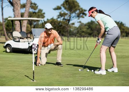 Woman playing golf while standing by man on field