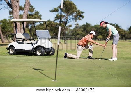 Man teaching woman playing golf while kneeling on field