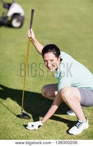 Portrait of woman holding golf club while crouching on field