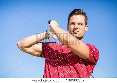 Low angle view of golfer man taking shot while standing against clear sky
