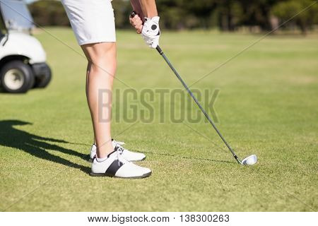Low section of young man playing golf while standing on field
