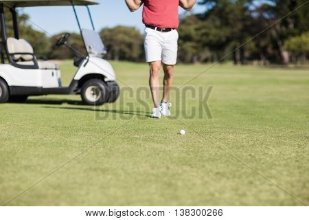 Low section of man by golf buggy while standing on field