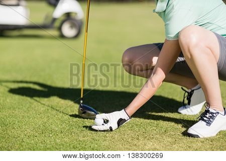Low section of woman holding golf ball while crouching on field