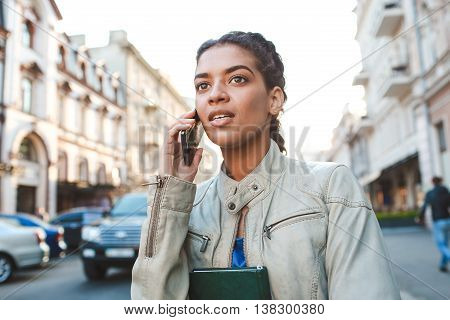 Attractive girl dressed in blue t-shirt and grey jacket talking on the phone, hold the book and catching the car at the street background.