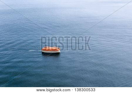 Lifeboat awaiting rescue in the wide expanse of the sea. Life boat is enclosed and rigid type rescue craft.