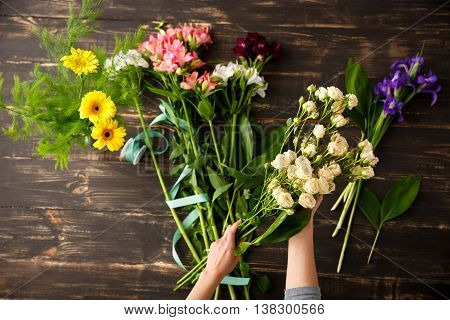 Bright colorful alstroemerias, irises and on wood table, roses in hands, herberas in vase. From above.
