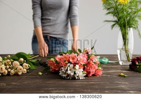 Girl in gray blouse and jeans prepare to make bouquet over gray background, hands and flowers on wood table. Focus on alstroemerias and roses.