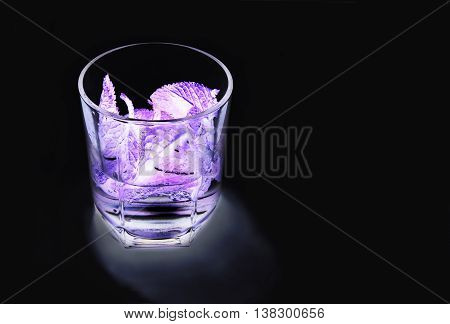 alcoholic cocktail with mint, lemon and gin in ultraviolet light