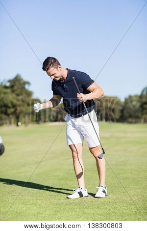 Golfer clenching fists while standing on golf course