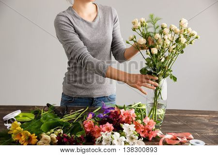 Girl  in gray blouse and jeans make a bouquet over gray background, putting roses in vase, flowers and vase on wood table.
