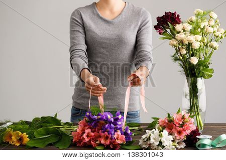 Girl in gray blouse and jeans make bouquet over gray background, prepare to put alstroemerias and irises in vase, flowers and vase on wood table, roses in vase.