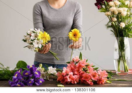 Girl in gray blouse and jeans make bouquet over gray background, prepare to put alstroemerias and herberas in vase, flowers and vase on wood table.