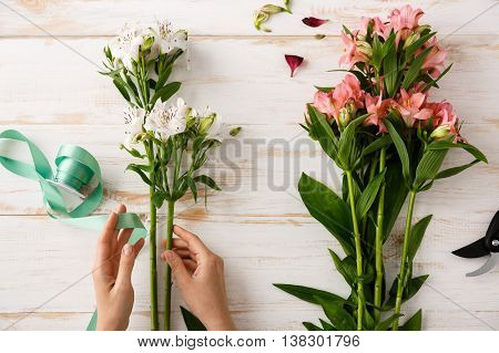 Bright colorful alstroemerias and green ribbon in hands on wood table. From above.