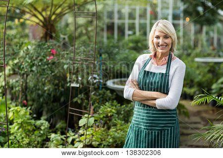 Portrait of confident mature gardener standing by plants