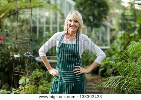 Portrait of happy mature woman standing with hand on hip at greenhouse