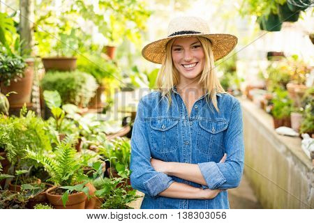 Portrait of confident young female gardener at greenhouse