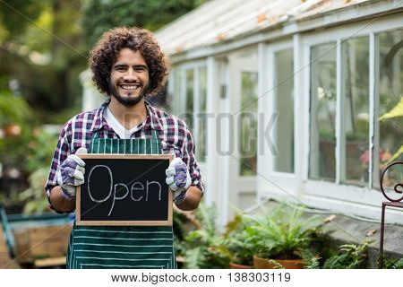 Portrait of happy male gardener holding open sign placard outside greenhouse
