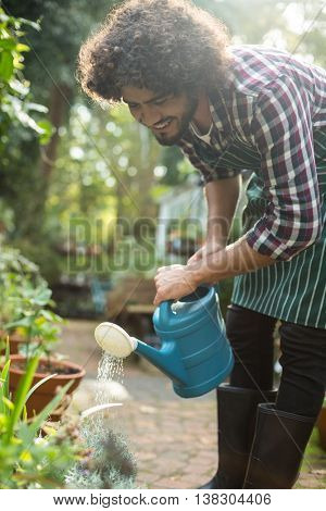 Happy male gardener watering plants outside greenhouse