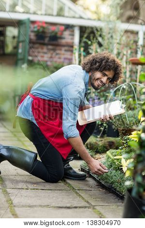 Portrait of happy male gardener with clipboard working outside greenhouse