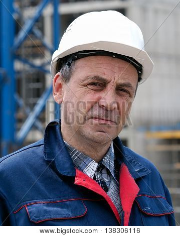 Portrait of a male builder engineer on the background of a construction site. The white helmet overalls. Wrinkles tired experienced look