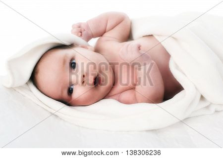 Newborn baby with open keen eyes laying in his bed with white background