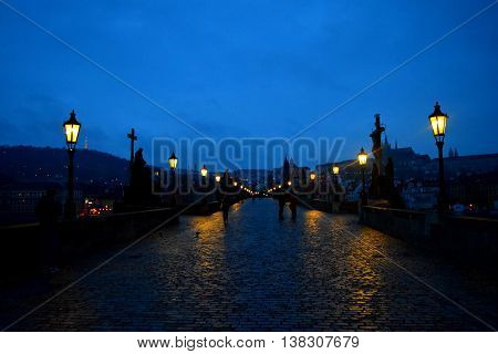 The Charles Bridge at foggy dusk with the lights on and wet road from rain.