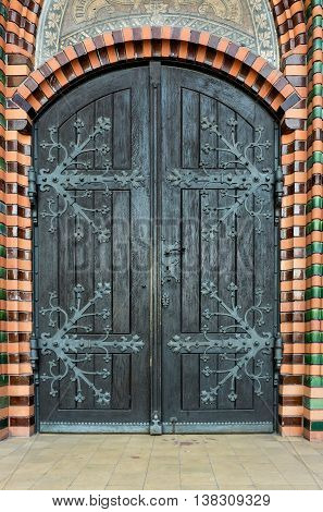 Massive wooden church door with a handle forged with an iron grip settled into a brick wall at the church. Breclav. South Moravia