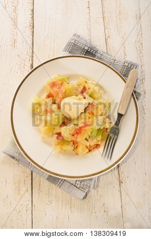 irish colcannon with butter made with mashed potato cabbage grilled bacon and crushes peppercorn fork on a plate