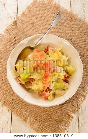 irish colcannon made with mashed potato cabbage grilled bacon and crushes peppercorn in a bowl with spoon