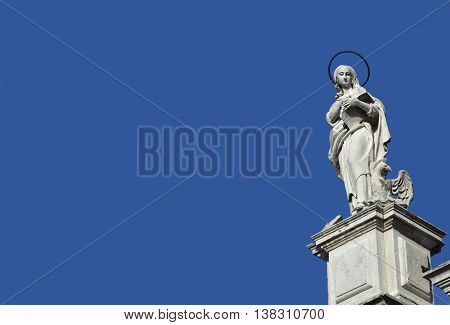 Statue of John the Evangelist and Apostle from baroque facade o Santa Maria Assunta jesuit church in Venice (18th century) with copy space