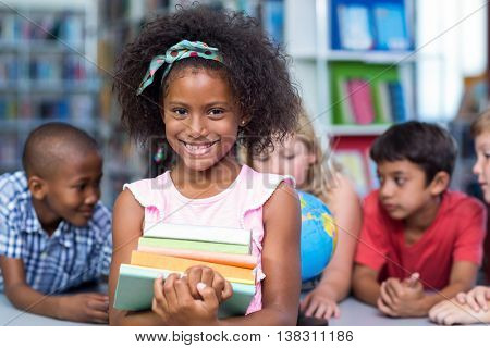 Portrait of smiling girl holding books against classmates in library