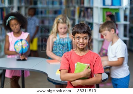 Portrait of boy holding books against classmates in library