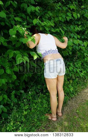 young woman sticking her head into bushes as if searching for something