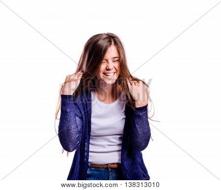 Teenage girl in white t-shirt and blue cardigan, touching hair, laughing, eyes closed, young beautiful woman, studio shot on white background, isolated