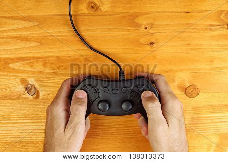 Man using game pad controller on wooden desk flat lay top view gaming and entertainment concept